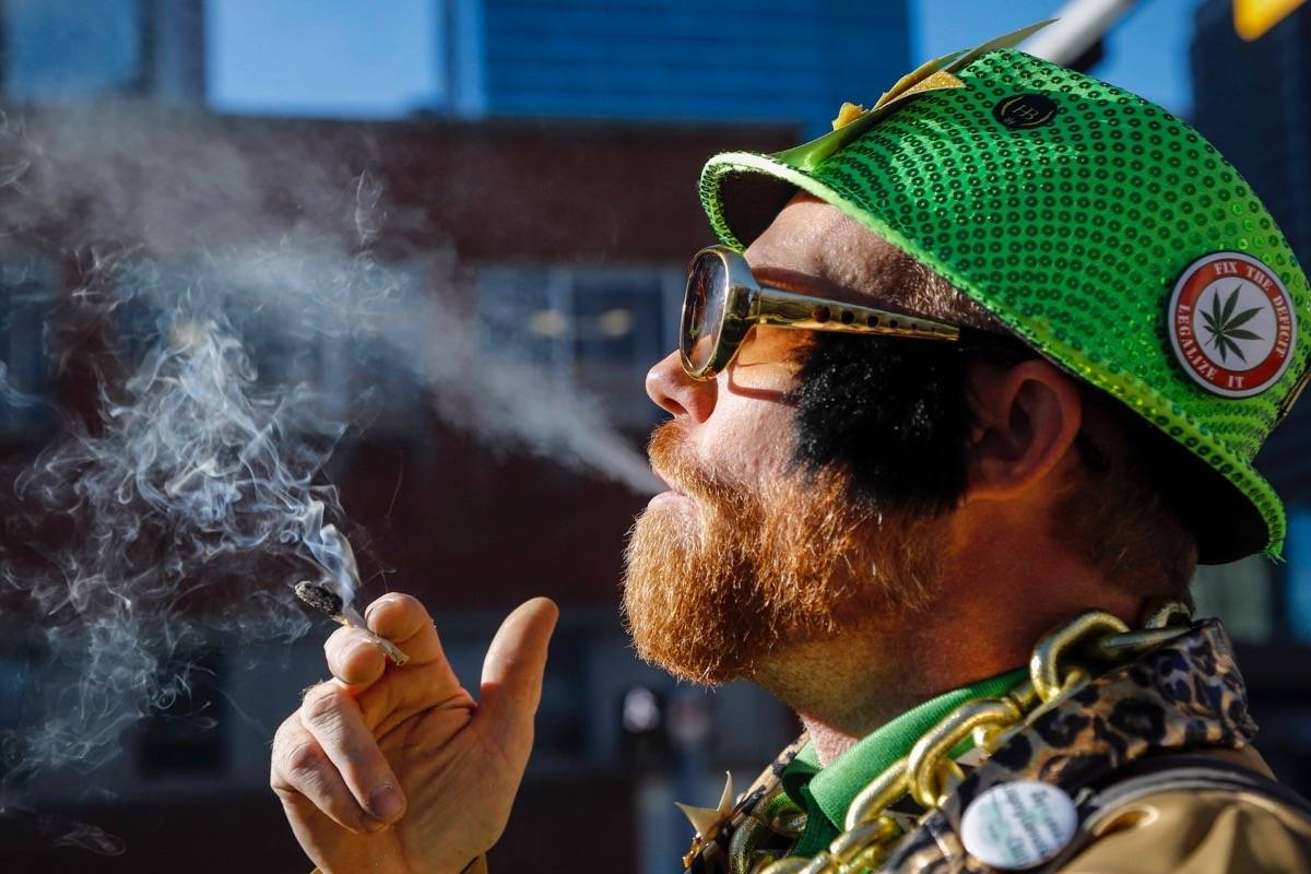 Cannabis user Scott Wells smokes a joint at a rally outside governments offices following the legalization of cannabis in Calgary, Alta., Wednesday, Oct. 17, 2018. (Jeff McIntosh/The Canadian Press)