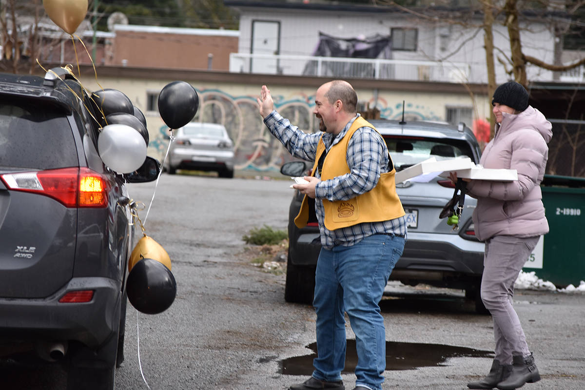 Dr. Joshua Greggain waves to a driver during a drive-thru goodbye parade at Hope Medical Centre on Friday, Feb. 26. Greggain gave out cookies bearing his likeness to parade-goers. (Photo/Adam Louis)
